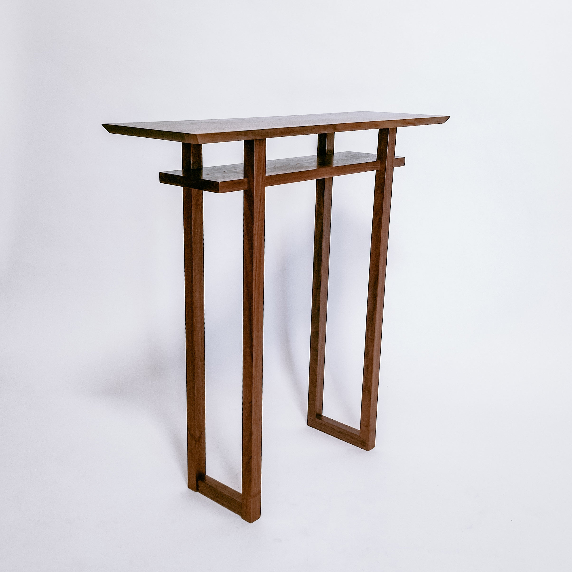A minimalist console table, handmade from walnut, featuring a live edge table top and inset shelf