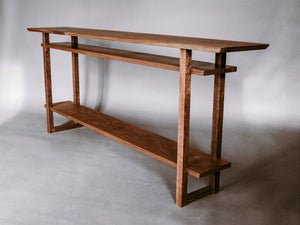 A hallway table in solid walnut modern wood furniture for the entryways