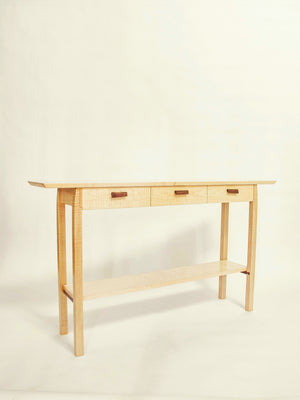 a narrow wooden table with drawers for the entry or hall