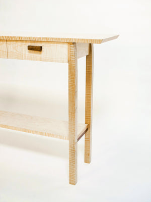 a narrow table with three drawers and a shelf for display