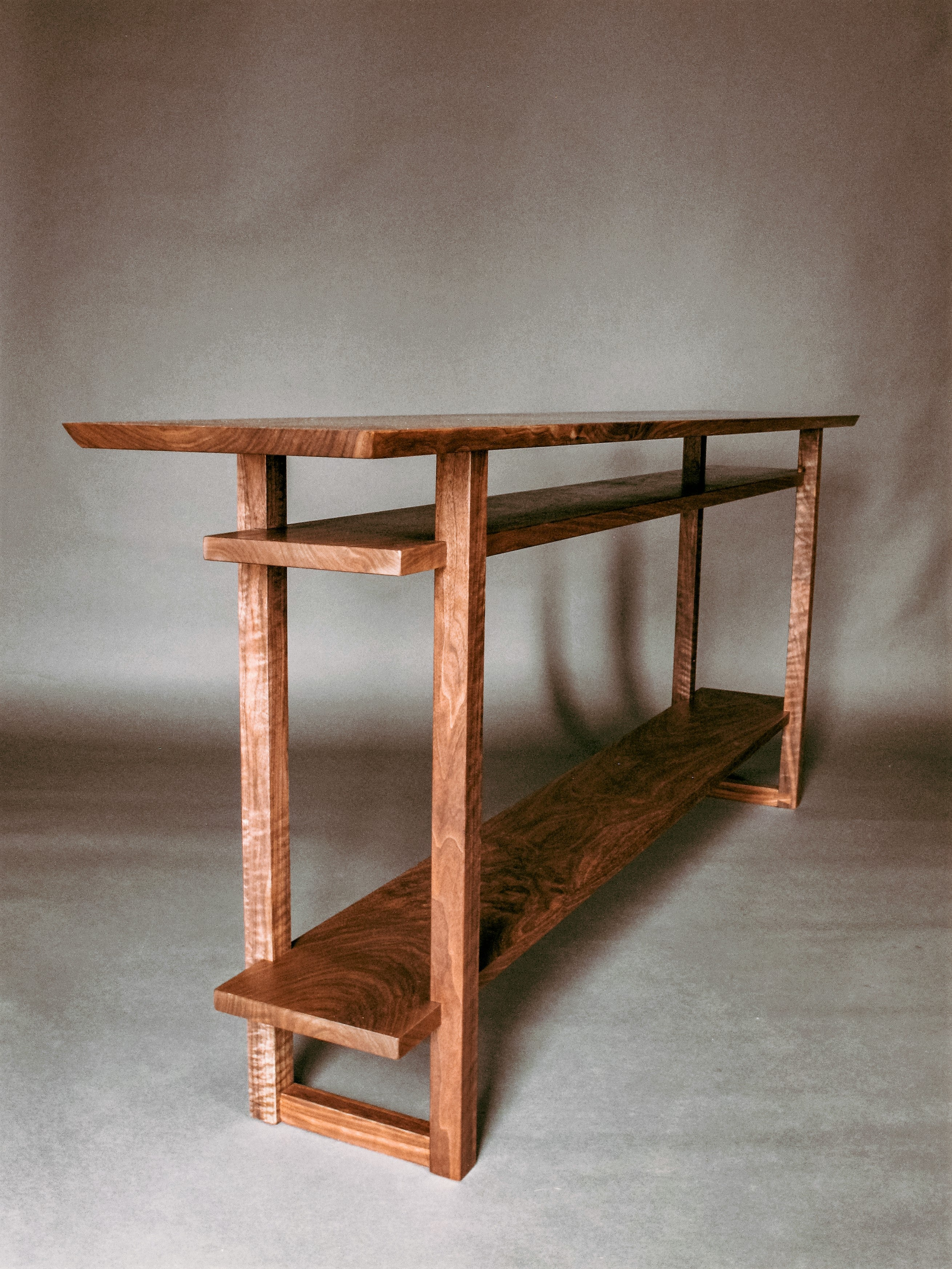 a long narrow console table with two shelves handmade from solid walnut wood