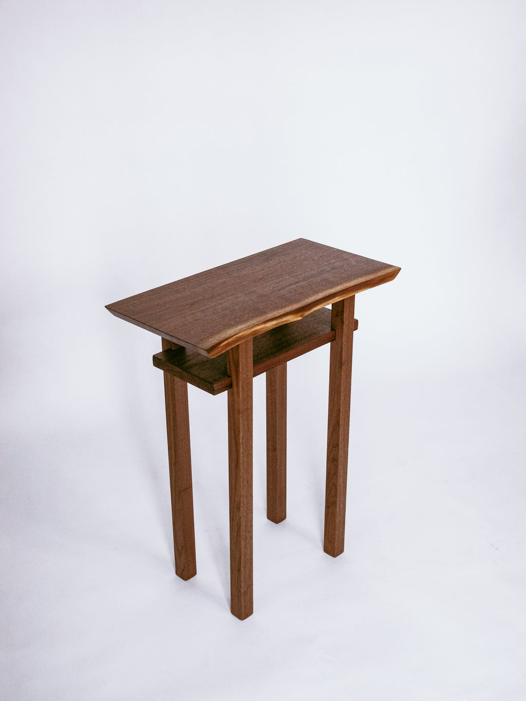 A narrow end table with shelf - live edge walnut table