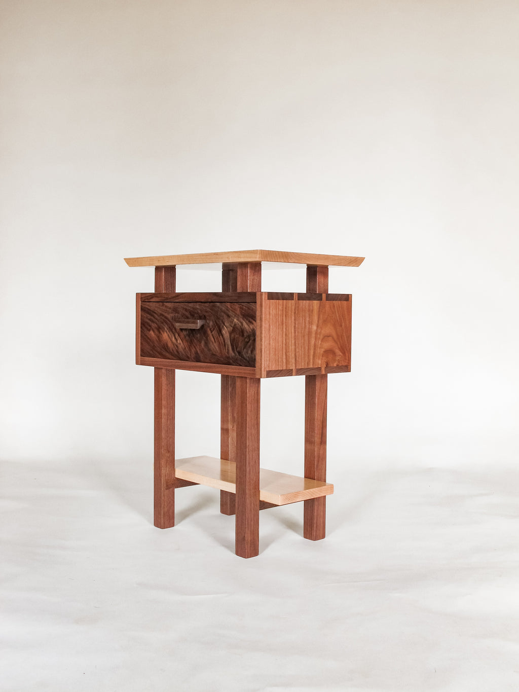 A small narrow nightstand made from walnut and tiger maple