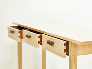 three narrow drawers at the top of our entry console table in tiger maple and walnut