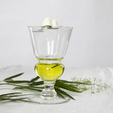 absinthe glass, absinthe in glass, spoon and sugar on glass, scattered green leaves, white background.
