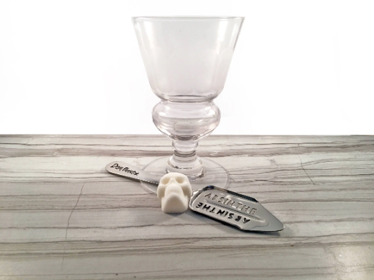 Absinthe Glass, Skull Sauger Cube and Absinthe Spoons on Light Background