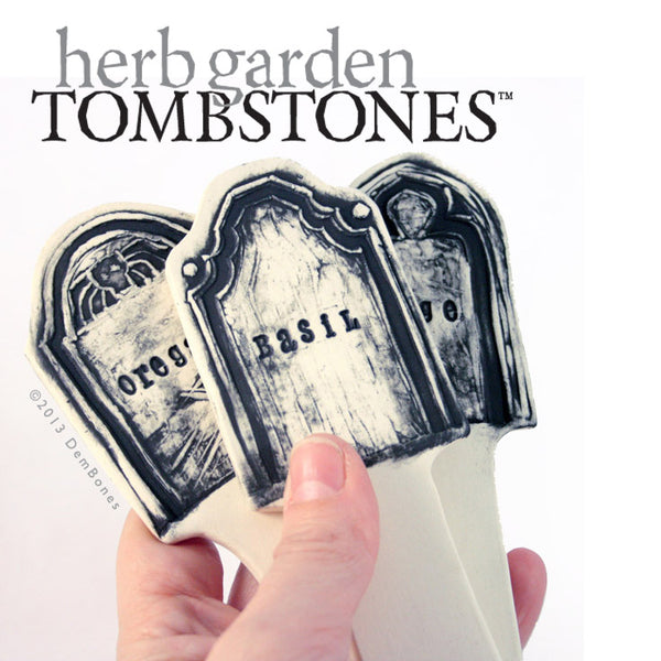 Basil, Oregano, and Sage Tombstone shaped plant stakes held in hand on white with text herb garden tombstones