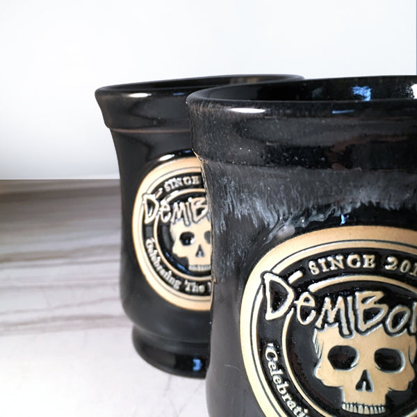 two stagered black ceramic mugs, cropped on right, Skull image, DemBones logo, light background.