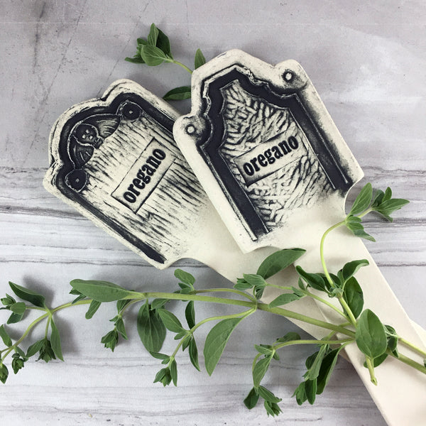 two ceramic herb marker tombstones on marble background with fresh oregano