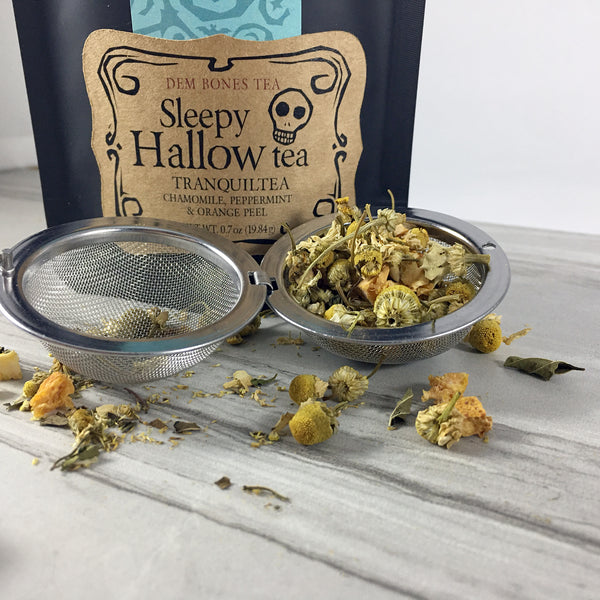 DemBones Sleepy Hallow Tea, Close up of tea in Tea ball , Dried Chamomile and mint close up on light background