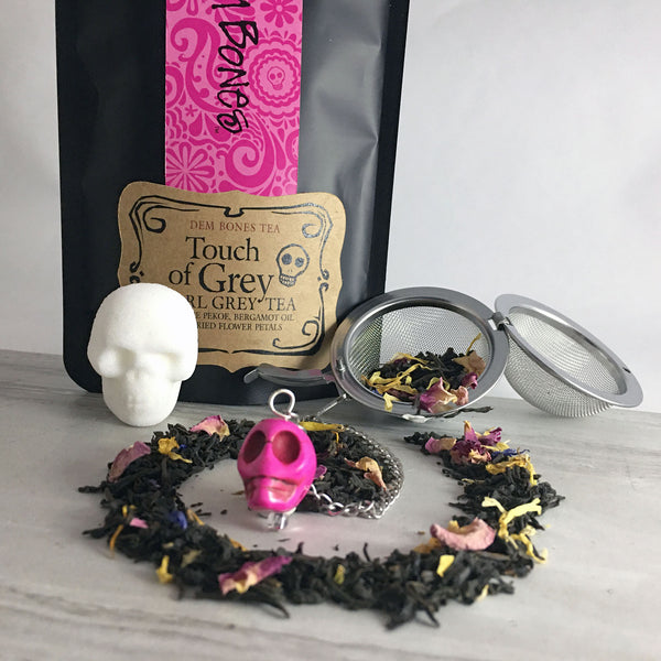 Black and Pink Tea Packaging, Ear grey tea in a swirl on light background, one skull shaped sugar cube, pink skull bead with Tea Infuser Ball