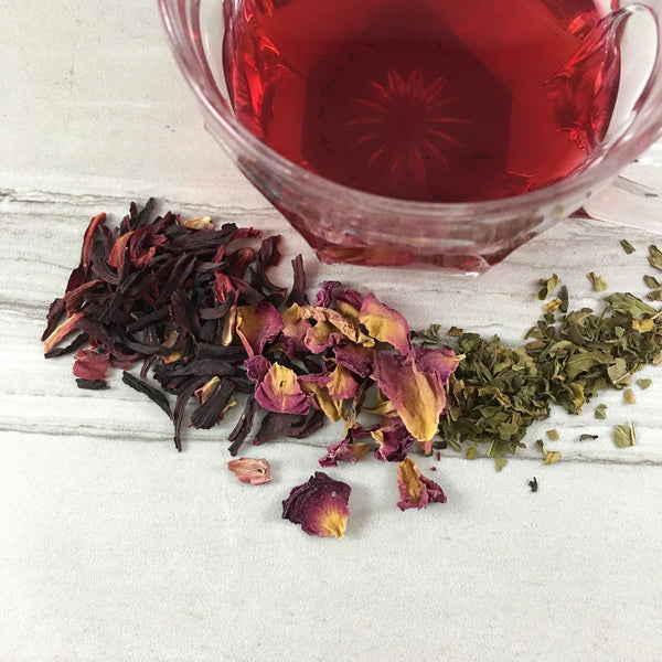 Tea spread on white tile, Red tea in vintage glass cup,  Dried Hibiscus Rose Petals and  Mint