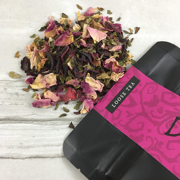 Rose tea spilled on marble table, black bag with deep pink label, loose tea, gothic design