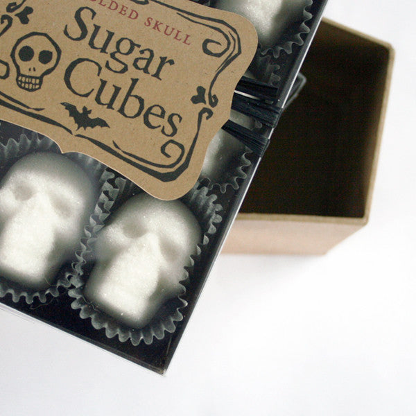 cropped black box, skull sugar cubes, paper candy cups, Sugar Cubes label, white background.