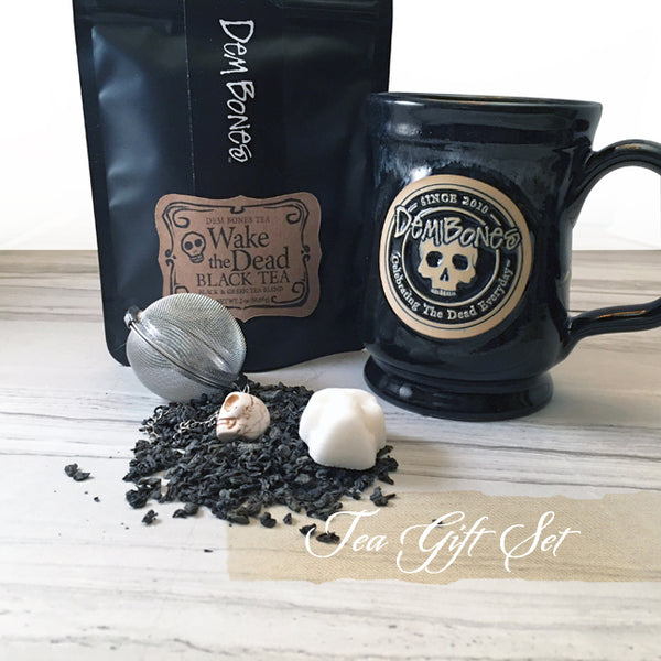 Black tea package, Black ceramic mug with round skull log, spilled tea, sugar cube skull, tea ball skull bead