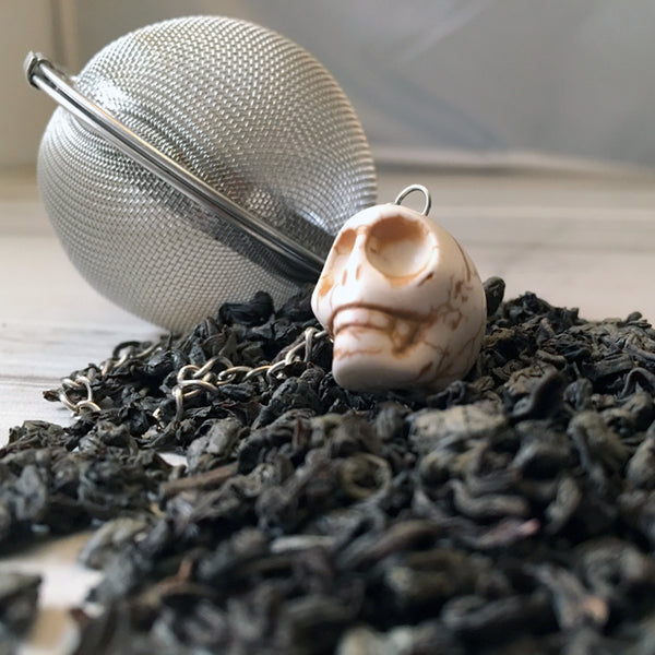 close up of tea with Tea ball and white skull bead