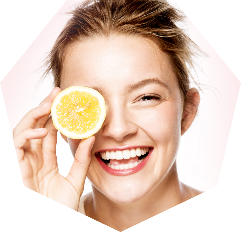 Smiling woman holding a slice of lemon over her eye