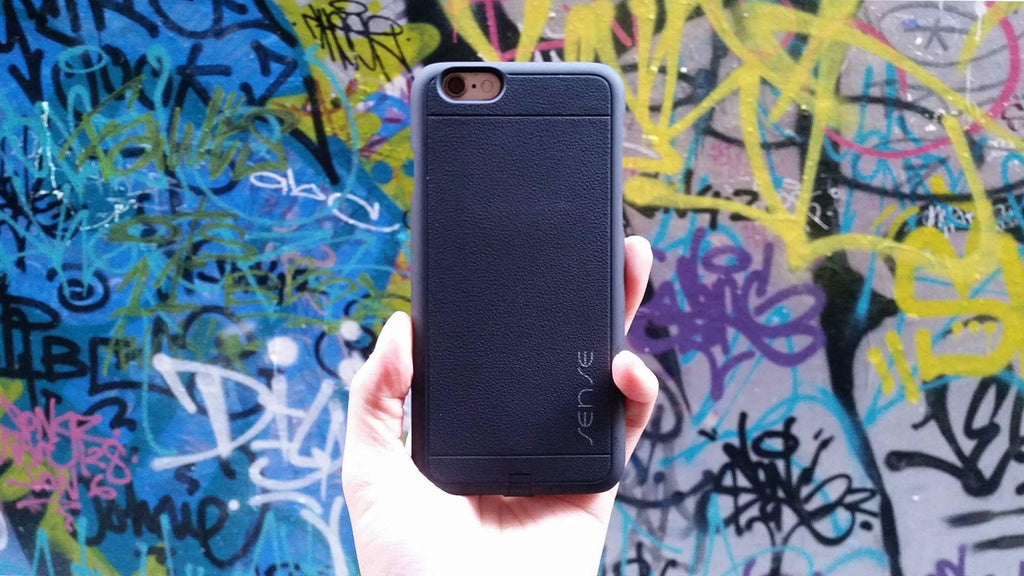 iphone recevier case black held up against graffiti wall