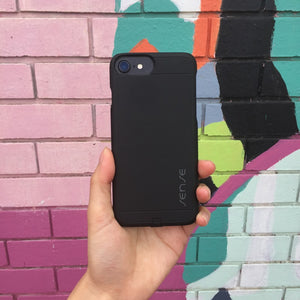 sense wireless iphone 7 receiver case onyx black being held in front of brightly coloured bricks