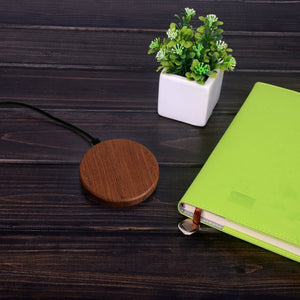 Sense wireless charger charging pad rose timber wood sitting on wooden desk with a small pot plant and notepad with green cover