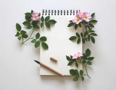 Note pad Booklet with a pencil and decorative flowers around it.