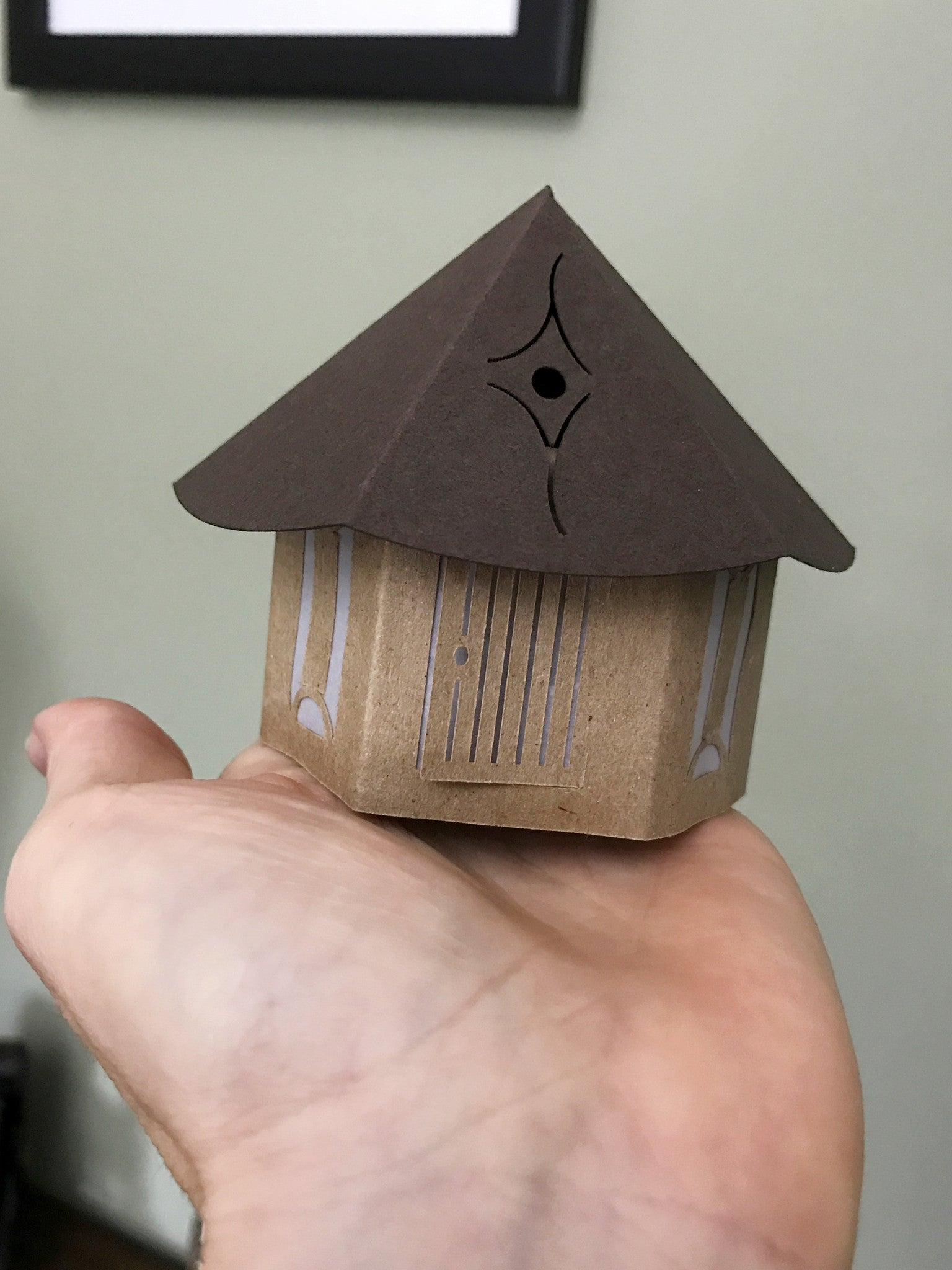 Tiny House Luminary in hand to show size dark brown with light brown roof