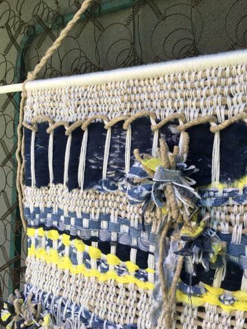 tie pompoms to center of woven wall hanging