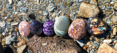 Colorful Polished crystals lined up on lake with rocks