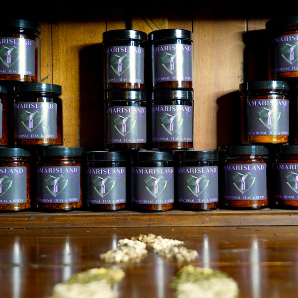 Jars of Amarisland Herbal Tea Blends lined up on Wooden Background
