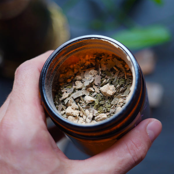 Powder of herbs and leaves of tea in an amber glass jar, held in the left hand over a black slate and meditation tools in the background