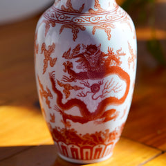 Macro photo of dragon painted on body of Vintage orange and white hand painted Japanese porcelain vase with  dragons, displayed on wood floor
