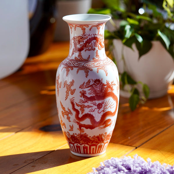 Vintage orange and white hand painted Japanese porcelain vase with  dragons, displayed on wood floor with potted plant in background