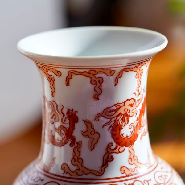 Macro photo of stem and rim of opening on vintage orange and white hand painted Japanese porcelain vase with dragons