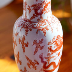 Close up of painted body of vintage orange and white hand painted Japanese porcelain vase with  dragons, displayed on wood floor