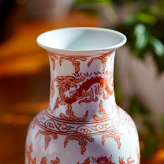 Close up photo of stem and rim of opening on vintage orange and white hand painted Japanese porcelain vase with  dragons, with potted plant in background