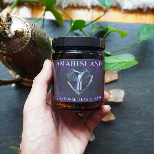 Jar of tea, labeled with AMARISLAND intentional teas and herbs, held gently in the left hand