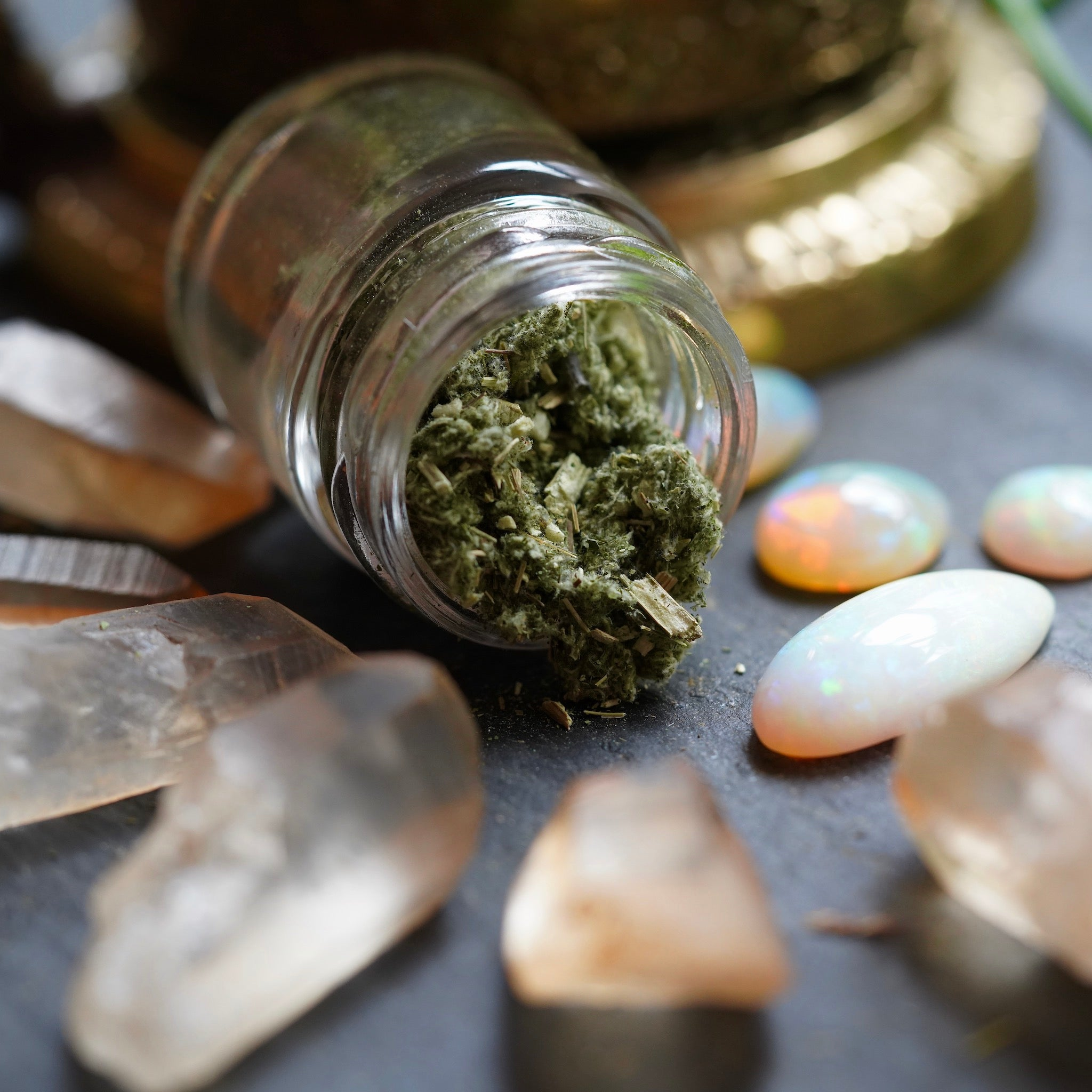 Raw Mugwort Herb spilling out of glass jar surrounded by Ethiopian opals and Hematite Quartz Crystal Points on a black background