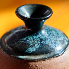 Macro photo of of black, white, and blue nebula glaze on top of a handmade brown clay ceramic bud vase, displayed on a light wood floor background