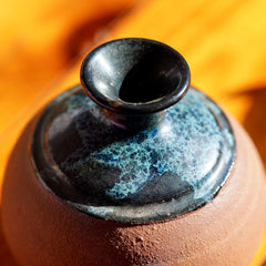 Close up shot of top rim and glaze on a handmade brown clay ceramic bud vase, displayed on a light wood floor