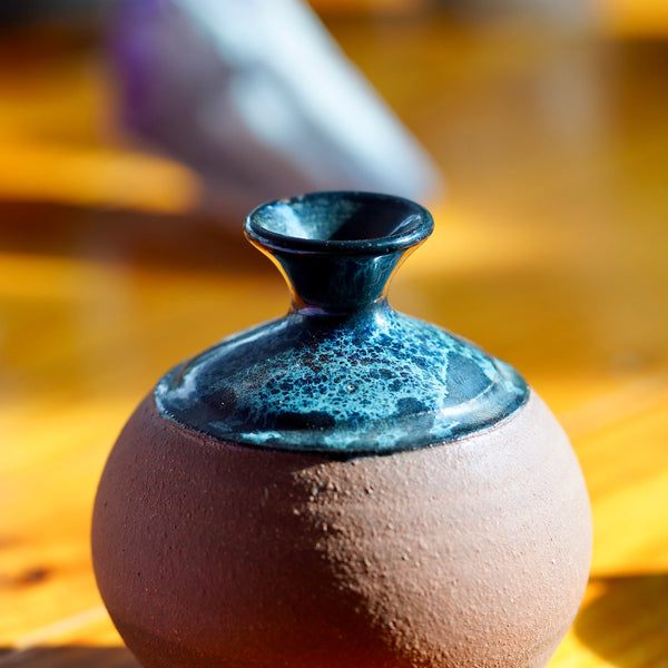Close up photo of black, white, and blue nebula glaze on top of a handmade brown clay ceramic bud vase, displayed on a light wood floor