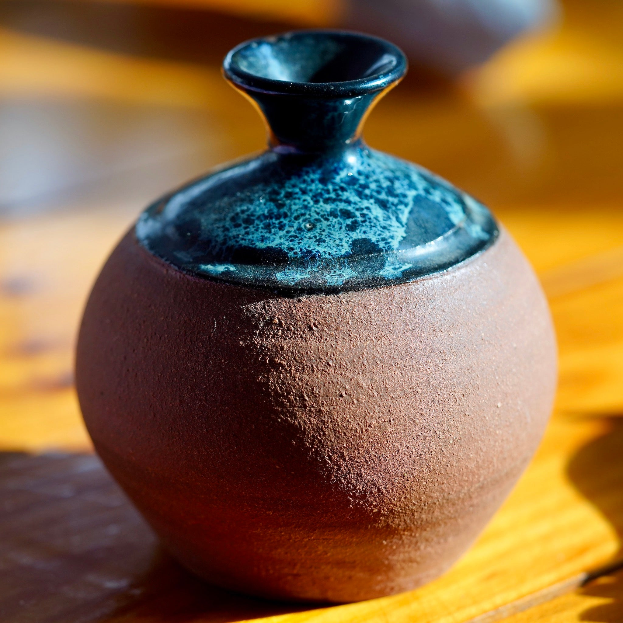 Handmade brown clay ceramic bud vase with black, blue and white nebula glaze on top, displayed on a light wood floor