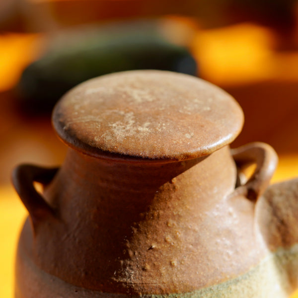 Macro photo of removable lid on vintage brown ceramic clay jug for sale.