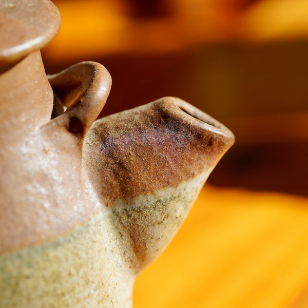 Macro photo of spout on vintage brown ceramic clay jug for sale.
