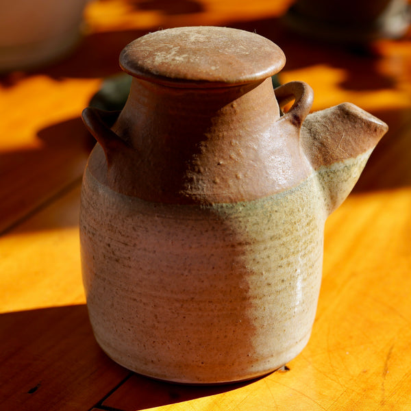 Vintage brown ceramic clay jug with a spout, two handles, and a removable lid, standing on a light wooden floor with shadows in the background