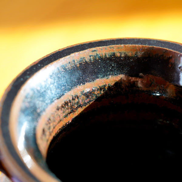 Macro shot of inner rim of ceramic jug, featuring a brown and black striped pattern glaze