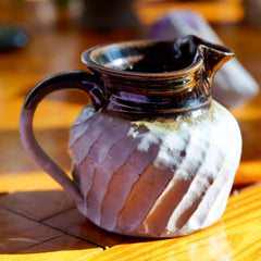 White and brown ceramic jug with handle and wavy pattern, sitting on wood floor and sunlit, with amethyst crystal laying in background