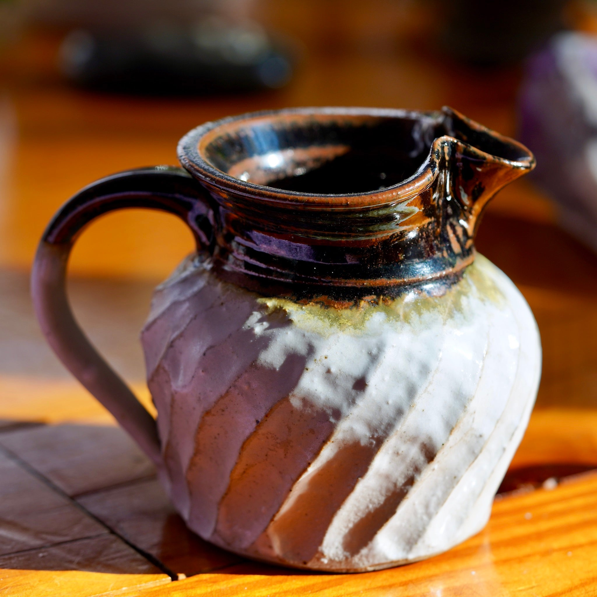 White and brown ceramic jug with handle and wavy pattern, sitting on wood floor and sunlit