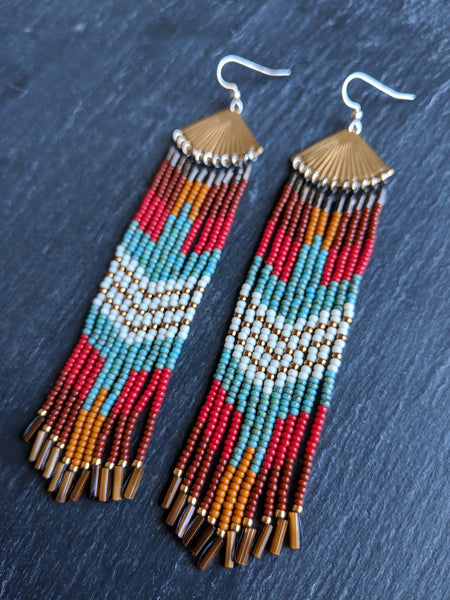 Long native beaded earrings with a colorful eagle design made with Czech glass beads, brass, and sterling silver ear wire