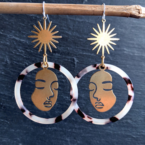 Moon & Milk - Large blonde tortoise hoop earrings with a raw brass star and Picasso face figure