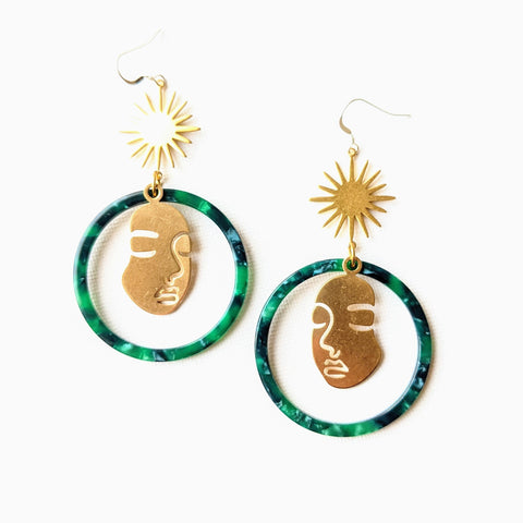 Moon & Milk - Large green tortoise hoop earrings with a Picasso face silhouette and a golden brass star charm.